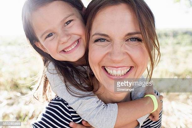 Portrait of mature woman giving daughter piggy back in park