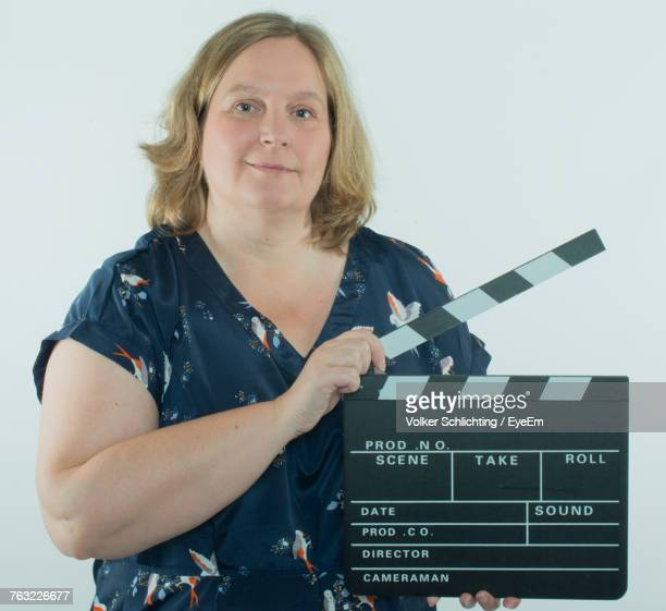 Portrait Of Mature Woman Holding Film Slate Against White Background