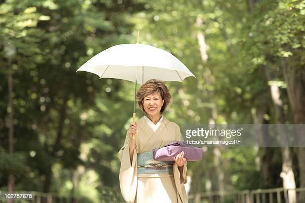 Portrait of mature woman in Kimono holding umbrella and gift, Kyoto city, Kyoto prefecture, Japan