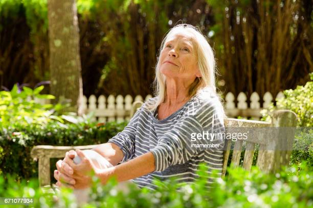 Portrait of mature woman looking up, sitting in the park