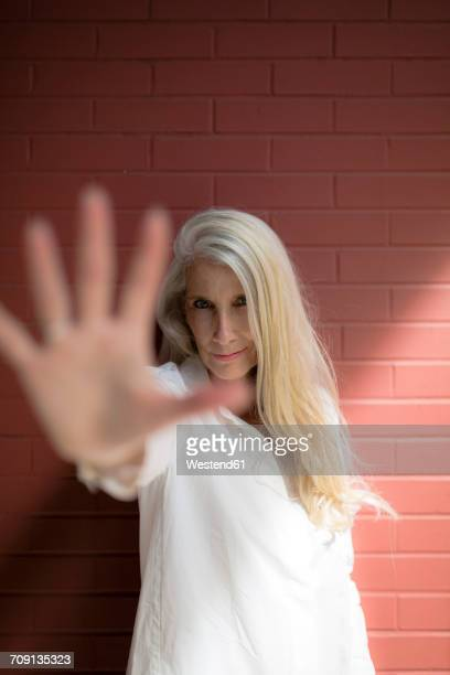 Portrait of mature woman raising her hand