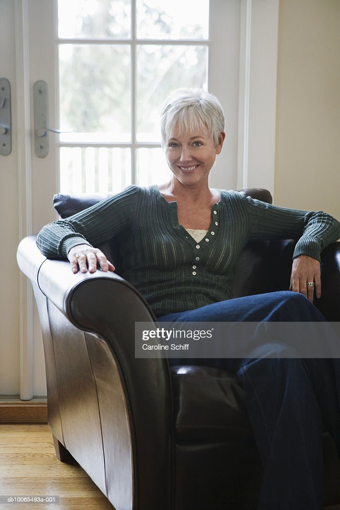 Portrait of mature woman sitting in armchair, smiling : Stock Photo
