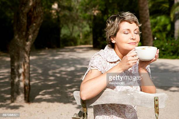 Portrait of mature woman sitting in the garden with cup of Cappuccino