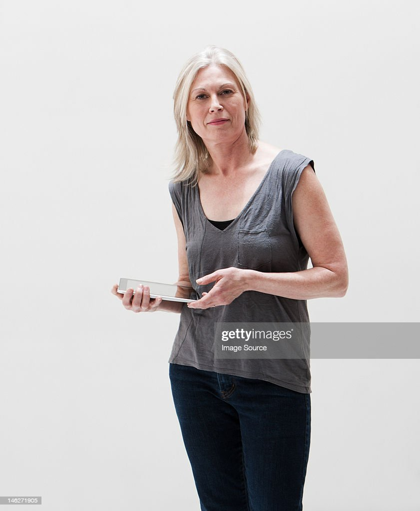 Portrait of mature woman using digital tablet, studio shot
