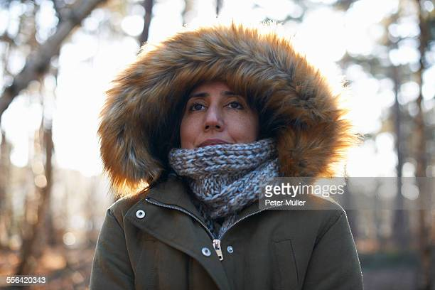 Portrait of mature woman wearing fur hood and scarf in forest