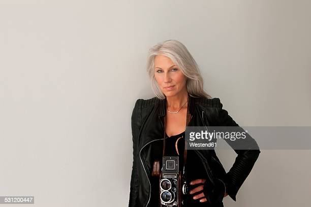 Portrait of mature woman with a vintage camera leaning at a wall
