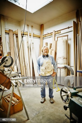 Portrait of mature woodworker standing in woodshop