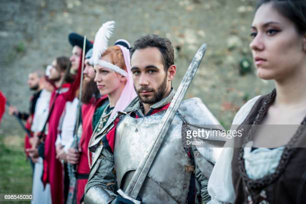 Portrait of medieval knight surrounded by peasants and aristocracy