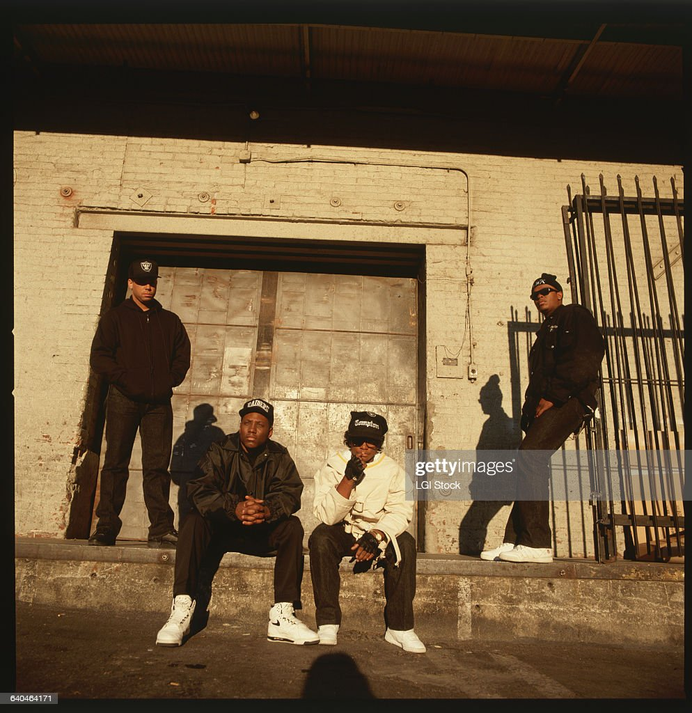 Portrait of members of the rap group, NWA, including DJ Yella, MC Ren, Eazy-E (center, wearing straitjacket), and Dr. Dre (right, wearing sunglasses).