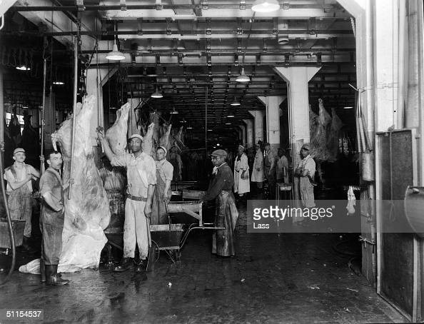 Portrait of men at a slaughterhouse as they stand near hanging beef carcasses late 1940s