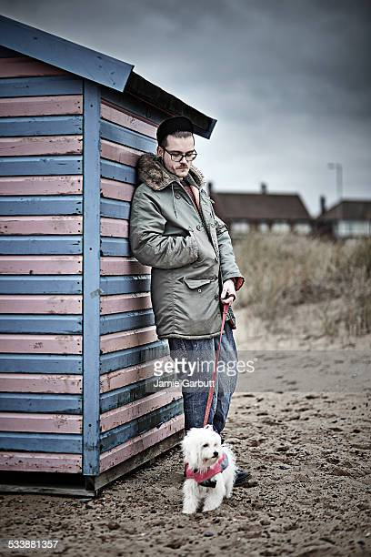 Portrait of mid 20's male and his dog leaning