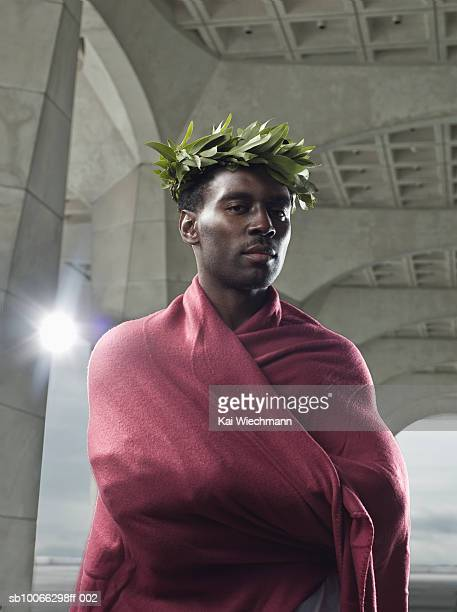Portrait of mid adult athlete in laurel wreath wrapped in purple cloth