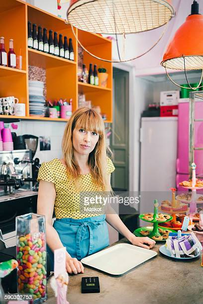 Portrait of mid adult barista standing at counter