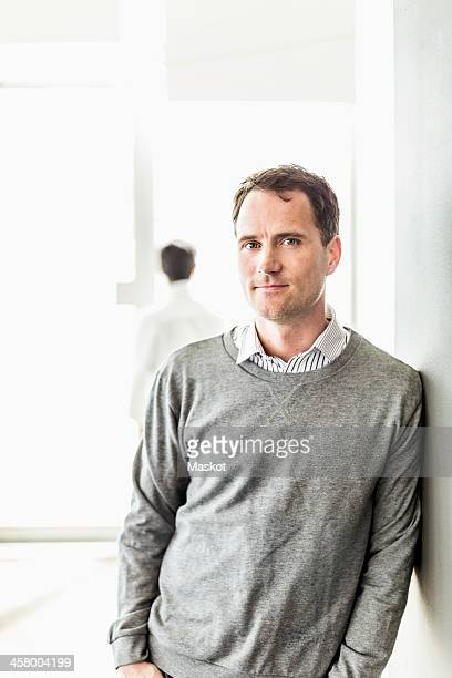 Portrait of mid adult businessman leaning on wall in office