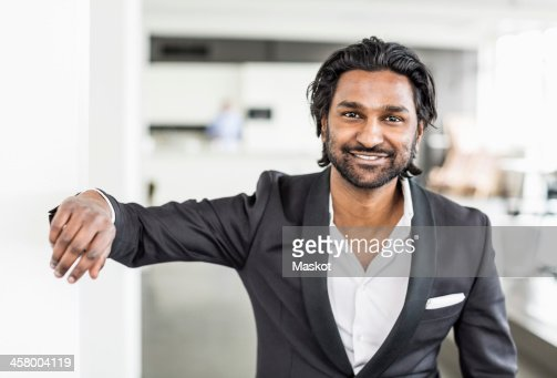 Portrait of mid adult businessman smiling while leaning on wall in office