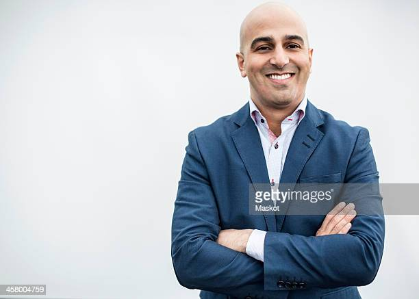 Portrait of mid adult businessman smiling while standing arms crossed against wall