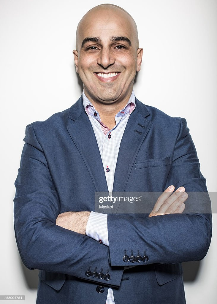 Portrait of mid adult businessman standing arms crossed against wall in office : Stock Photo