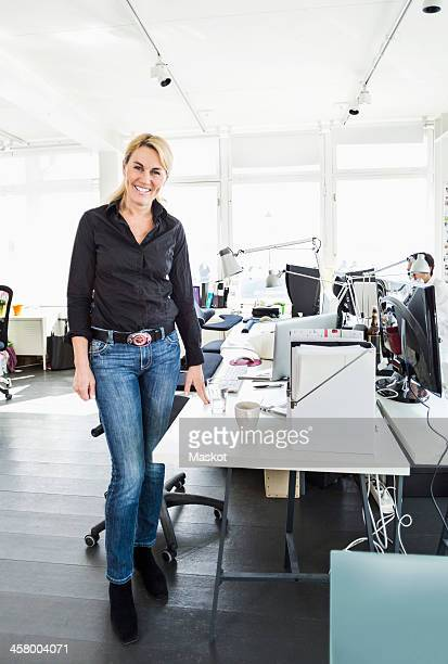 Portrait of mid adult businesswoman standing by desk in office
