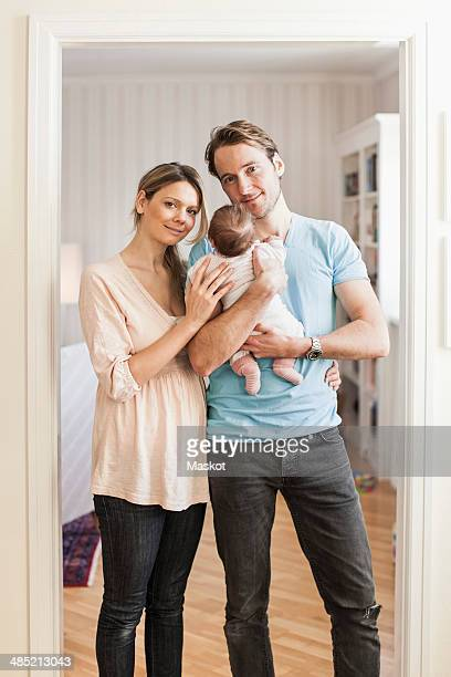 Portrait of mid adult coupe with baby girl at doorway
