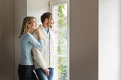 Portrait of mid adult couple looking out of window