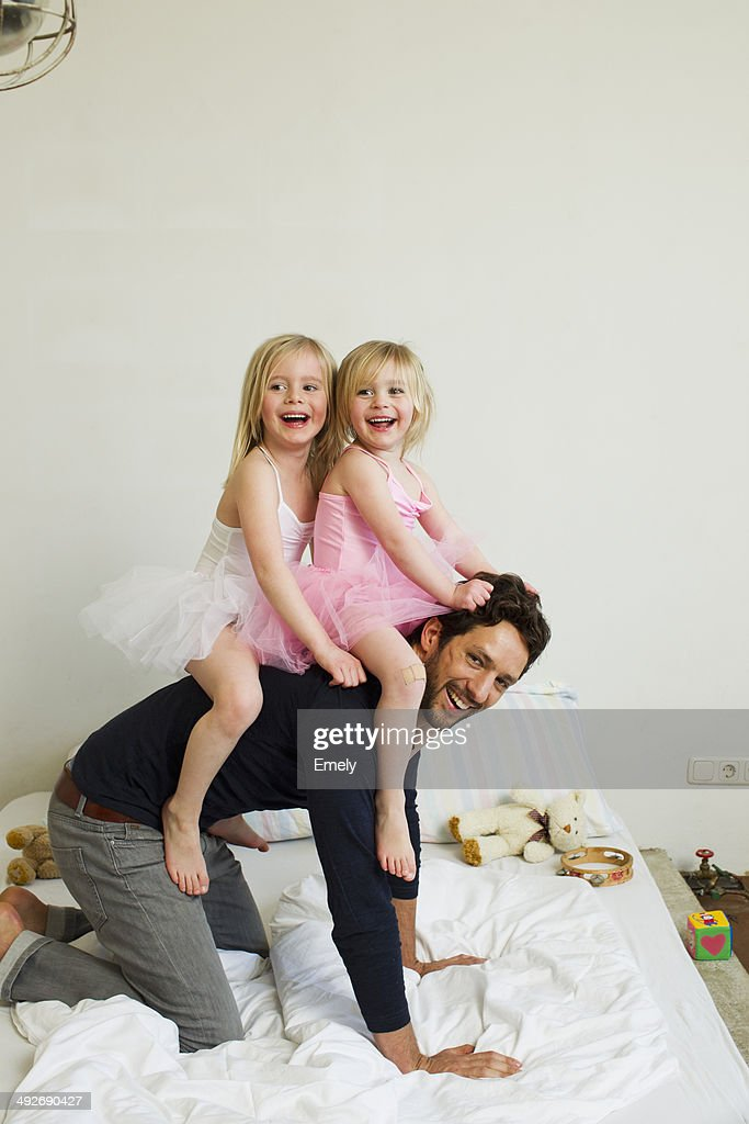 Portrait of mid adult father giving two young daughters a piggy back