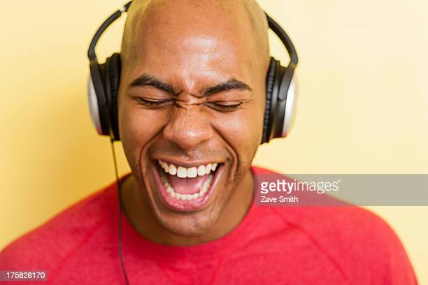 Portrait of mid adult male singing with headphones