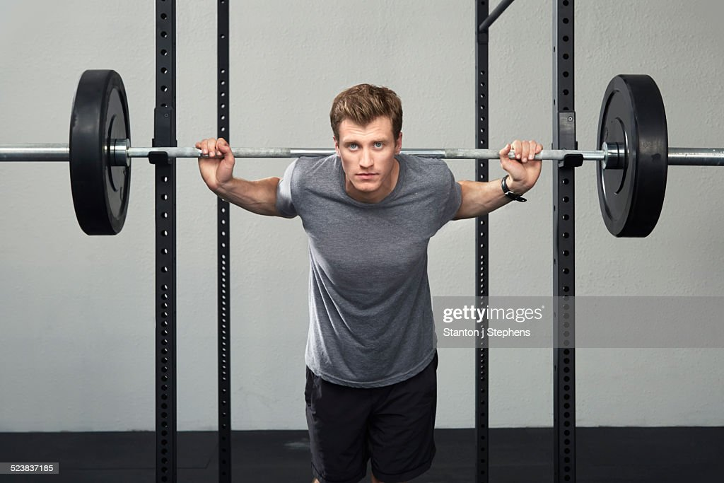 Portrait of mid adult male weightlifter lifting barbell in gym