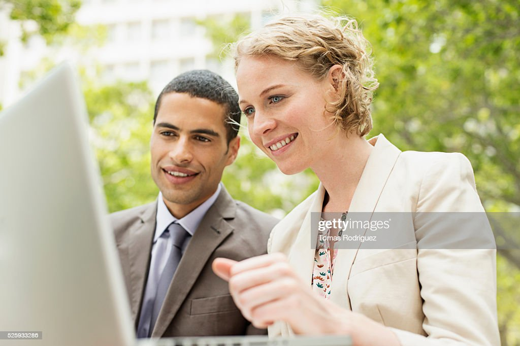 Portrait of mid adult man and woman working on laptop outdoor : Stock-Foto