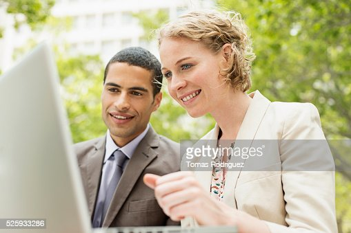 Portrait of mid adult man and woman working on laptop outdoor : Photo
