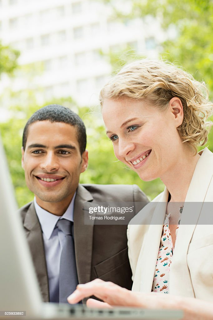 Portrait of mid adult man and woman working on laptop outdoor : Stock Photo