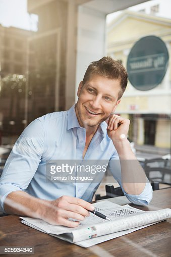 Portrait of mid adult man doing crossword puzzle in cafe : Stock Photo