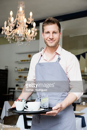 Portrait of mid adult man holding tray with dishes : Stock Photo
