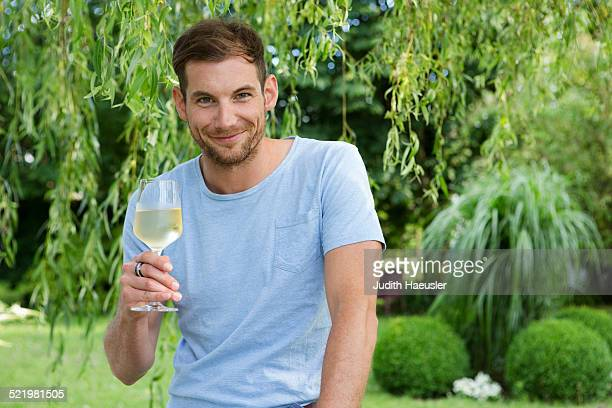 Portrait of mid adult man holding up a glass of white wine in garden