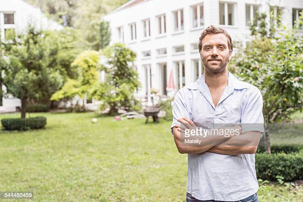 Portrait of mid adult man in front of house
