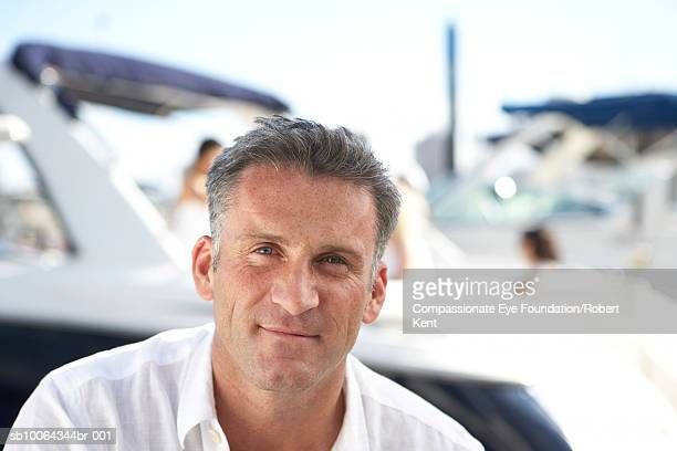 Portrait of mid adult man in front of yacht