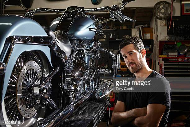 Portrait of mid adult man in motorcycle repair workshop