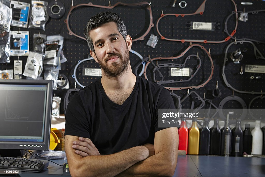 Portrait of mid adult man in motorcycle shop : Stock Photo