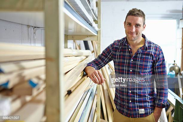 Portrait of mid adult man leaning against shelves in picture framers workshop