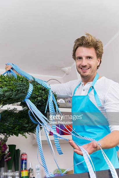 Portrait of mid adult man preparing floral wreath in flower shop, smiling