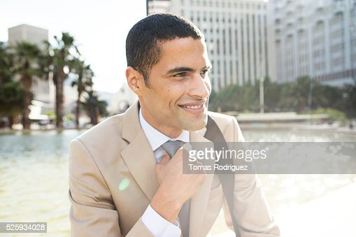 Portrait of mid adult man resting by fountain : Stockfoto