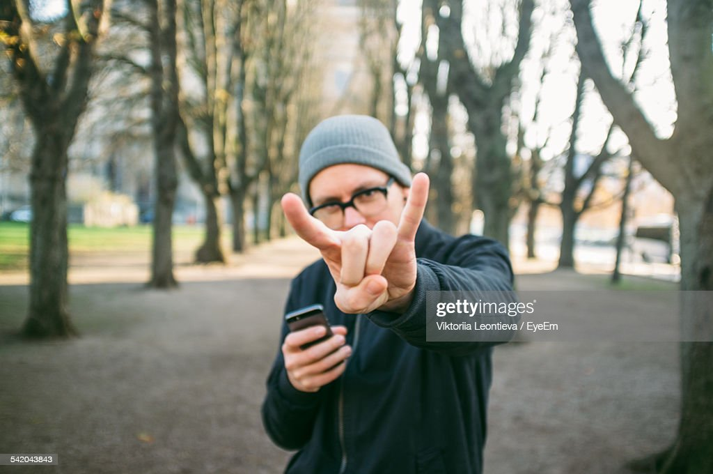 Portrait Of Mid Adult Man Showing Rock Sign In Park