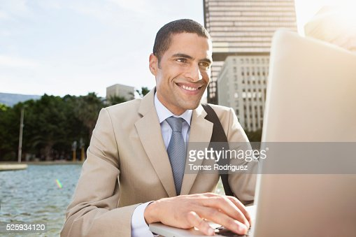 Portrait of mid adult man sitting by fountain and using laptop : Stockfoto