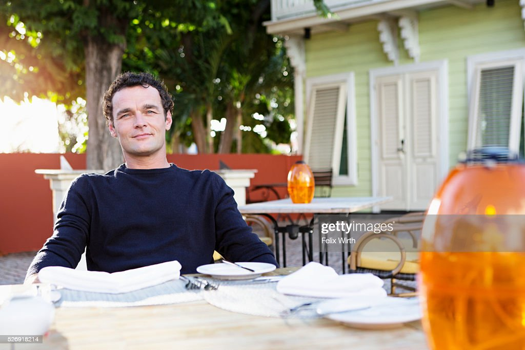 Portrait of mid adult man sitting in outdoor restaurant : Stockfoto