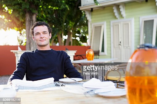 Portrait of mid adult man sitting in outdoor restaurant : Stock Photo