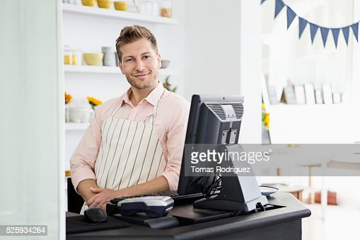 Portrait of mid adult man standing by checkout counter : Foto de stock