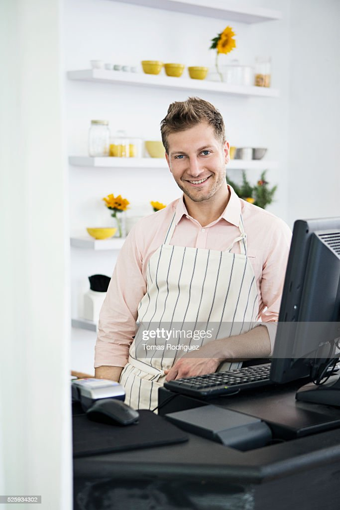 Portrait of mid adult man standing by checkout counter : Foto stock
