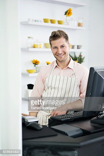 Portrait of mid adult man standing by checkout counter : Stock Photo