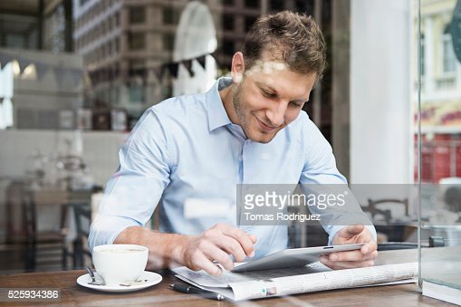 Portrait of mid adult man using digital tablet at cafe : Foto de stock