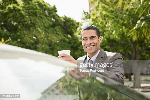 Portrait of mid adult man with coffee cup leaning on car : Bildbanksbilder