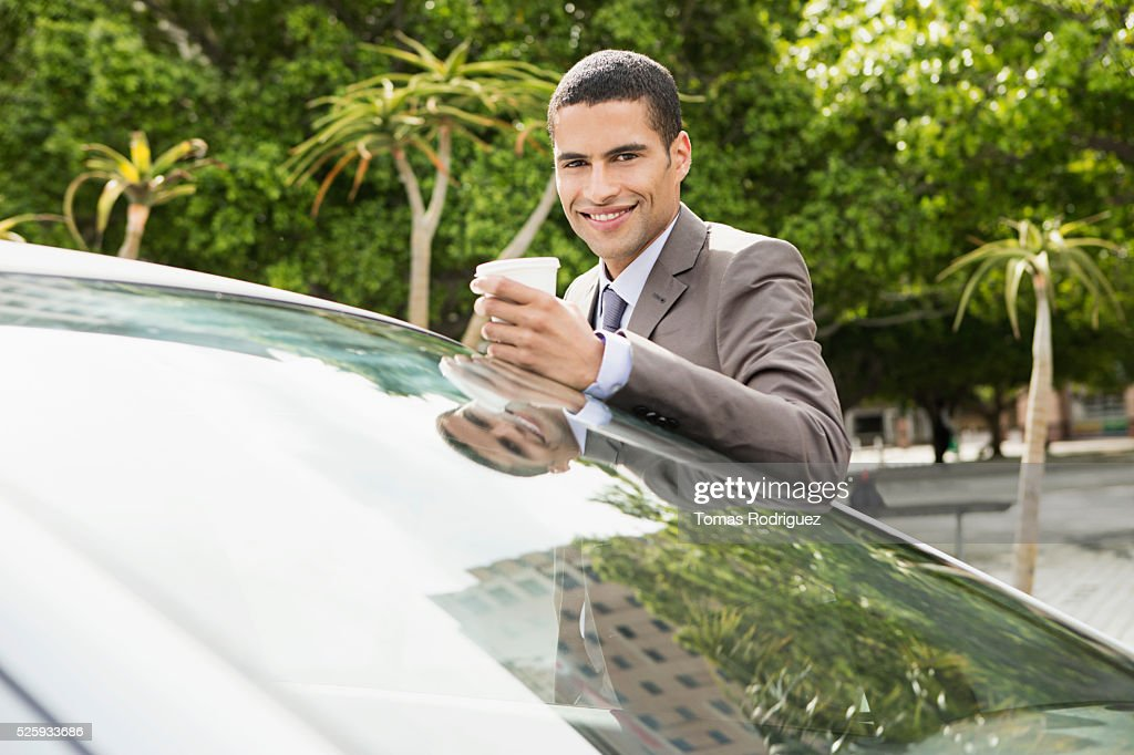 Portrait of mid adult man with coffee cup leaning on car : Stock Photo